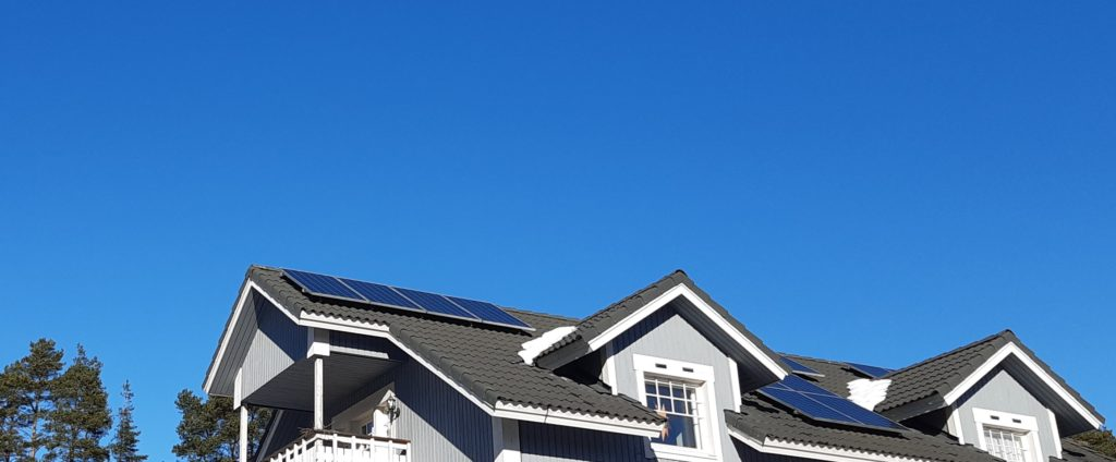 Aurinkopaneleja harmaan omakotitalon katolla.
