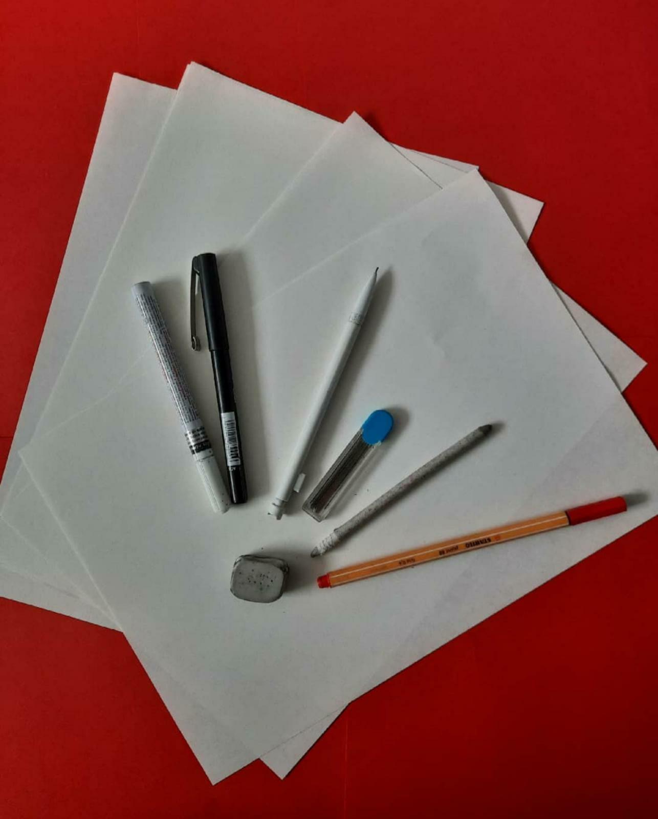 Kuvassa punainen tausta, kyniä ja ja paperia.