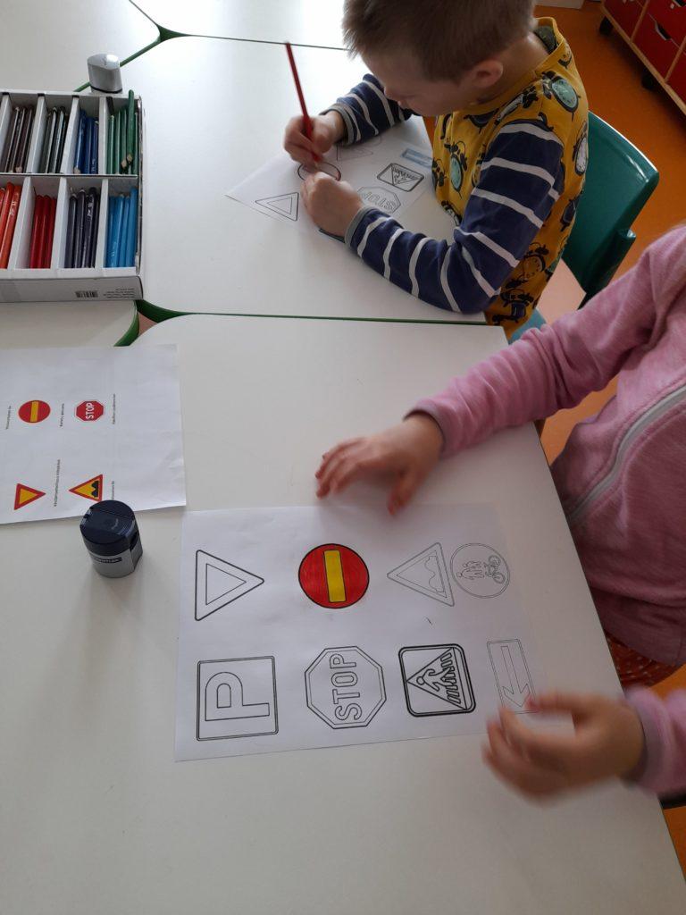 lapset värittävät liikennemerkkejä