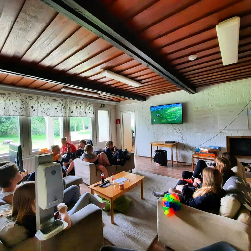 Kuvassa nuoria katsomassa jalkapalloa televisiosta
