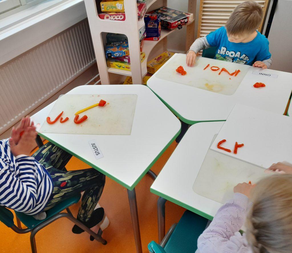 Lapset muovailevat pöydässä