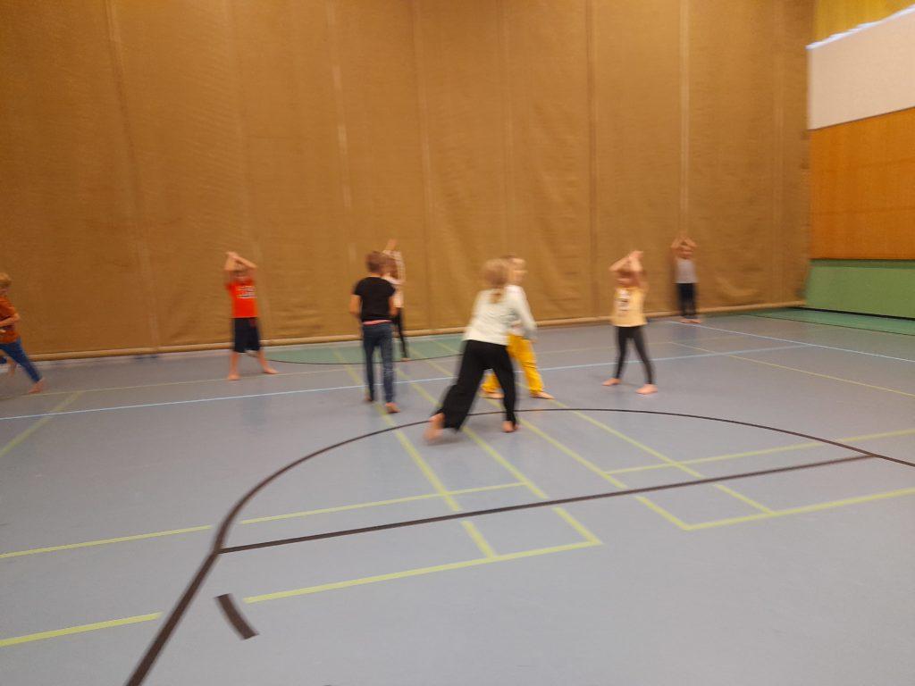 Lapset leikkivät liikuntasalissa.