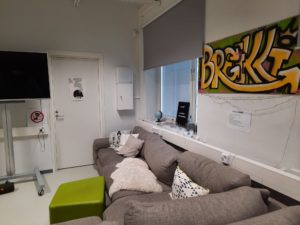 Kuvassa breikki tilan sohva ja taulu, jossa lukee Breikki