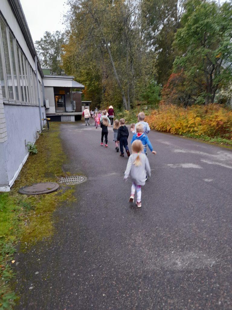 Lapset kulkevat jonossa aikuisen johdolla kokoontumispaikalle poistumisharjoituksessa