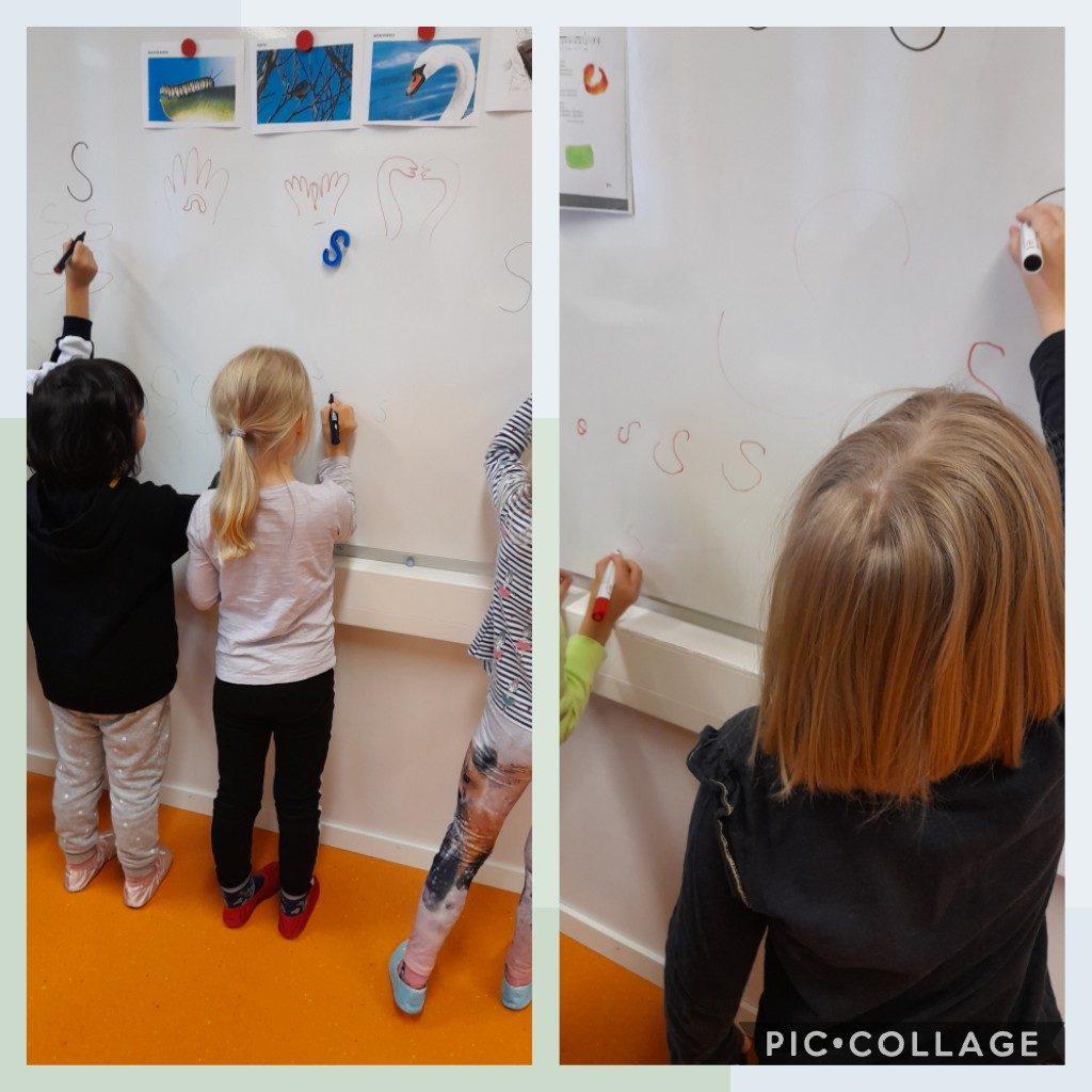 Lapset tekevät tussitaululle s-kirjaimia