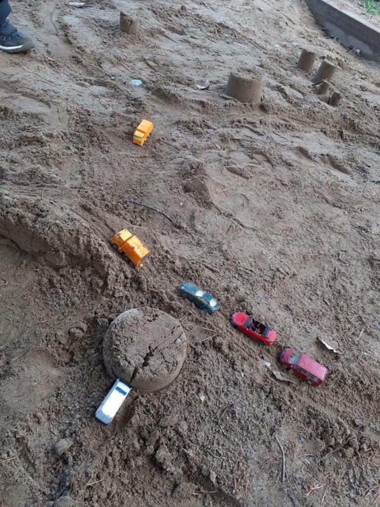 Lapset ovat rakentaneet pikkuautoille kaupungin hiekkalaatikolle