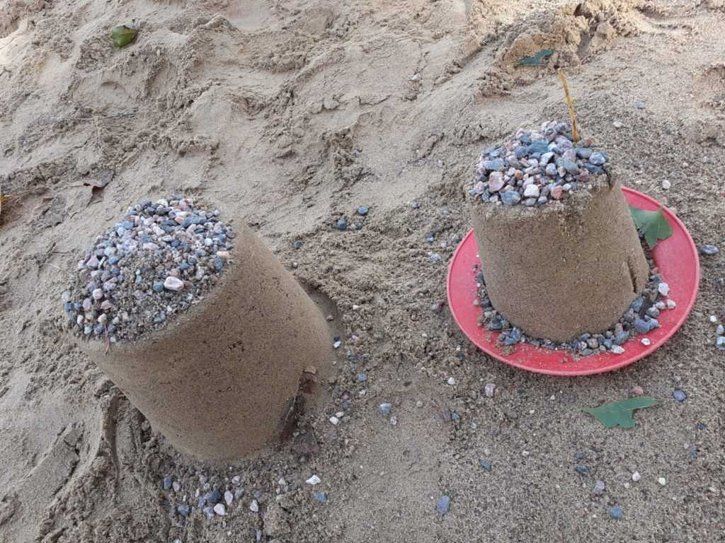 Kuvassa kaksi pikkukivillä koristeltua hiekkakakkua