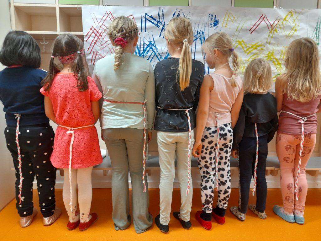 Lapset seisovat kuvassa ja heillä on letitetyt hännät vyötäröillä