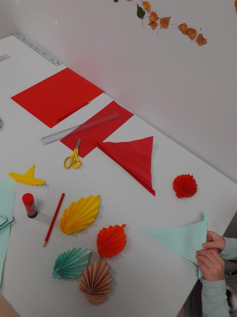 Lapsi taittelee väripaperista syksyn lehtiä